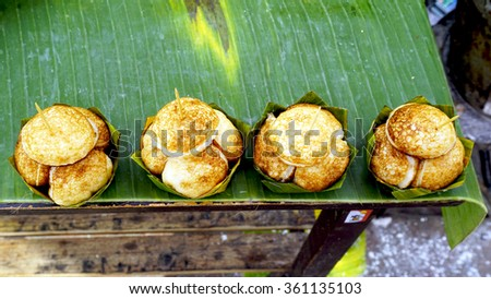 Sweet and Savory Grilled Coconut-Rice Hotcakes, Coconut Rice Cake on banana packaging, Asian dessert, Thai, Thailand, Luang Prabang, Laos - stock photo