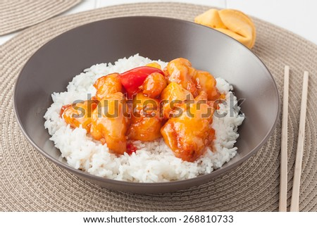 Sweet and sour chicken with rice in brown bowl - stock photo