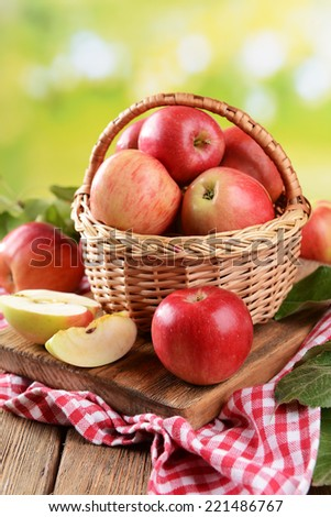 Sweet apples in wicker basket on table on bright background - stock photo