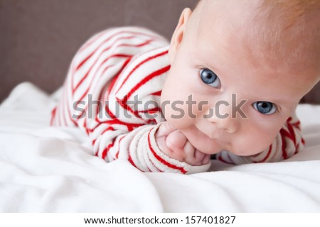 Sweet baby boy dressed in a striped sleepsuit lying with the fists under his head - stock photo