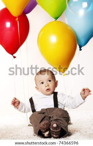 Sweet baby boy sitting on floor attached to colorful balloons. - stock photo