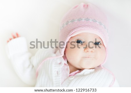 Sweet baby girl in a pink knitted hat - stock photo