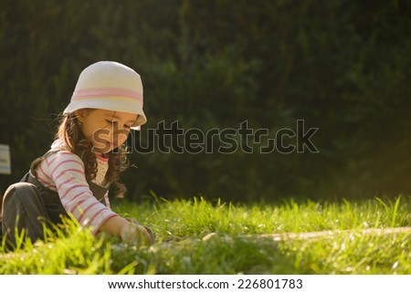 Sweet baby girl playing in sand on a sensory garden. Little girl enjoying nature. Outdoor playing. - stock photo