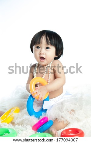 Sweet baby girl playing with toys over white background - stock photo