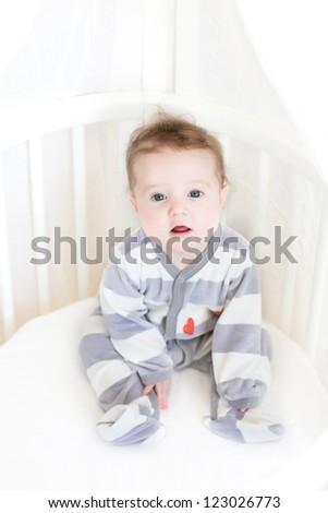 Sweet baby girl sitting in a white round crib - stock photo