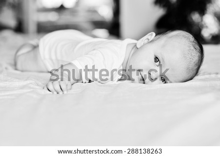 sweet baby is laying  on the bed - stock photo