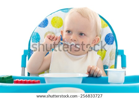 Sweet baby learning to eat with spoon sits on baby chair on a white background. - stock photo