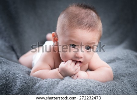 Sweet baby wearing diaper sucking on its finger - stock photo