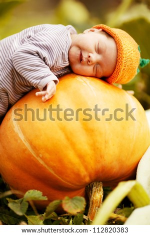 sweet baby with pumpkin hat sleeping on big orange pumpkin - stock photo