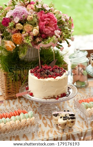 Sweet bar on summer wedding. Cake with protein cream and fresh berries on a cake stand outdoor - stock photo