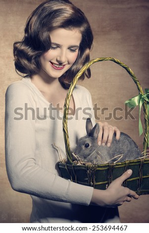 Sweet, beautiful, adorable, happy brunette woman is holding a easter basket with fluffy, cute rabbit. - stock photo