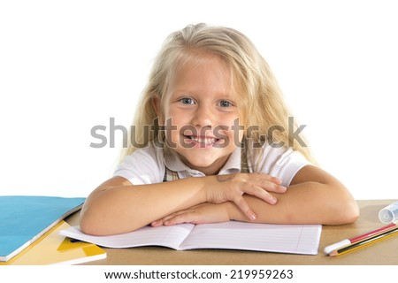 sweet beautiful little school girl with blonde hair sitting happy on desk leaning in relax on book or notepad in children education concept isolated on white background - stock photo