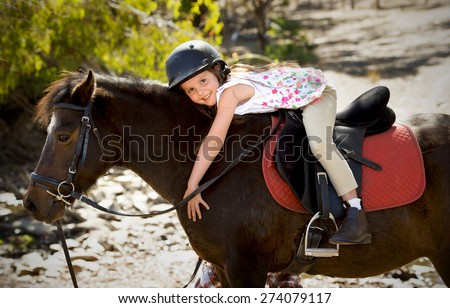 sweet beautiful young girl 7 or 8 years old riding pony horse hugging and smiling happy wearing safety jockey helmet posing outdoors on countryside in summer holiday - stock photo