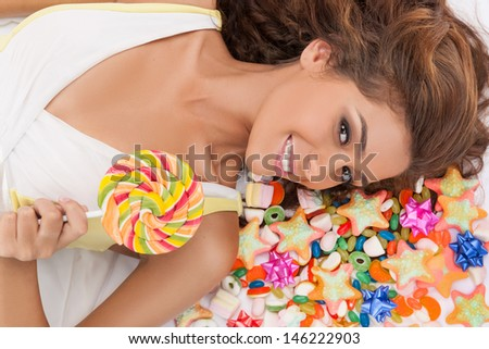 Sweet beauty. Top view of beautiful young women holding a lollipop while lying on the floor covered with candies - stock photo