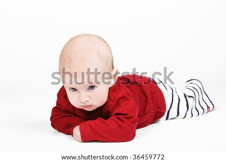 Sweet blue eyed baby against white background - looking a bit cross - stock photo