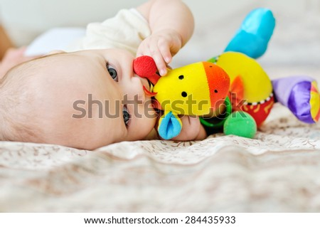 sweet blue-eyed baby biting a toy on the bed - stock photo