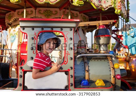 Sweet boy, riding in a train on a merry-go-round, carousel attraction in Europe, active children, summertime - stock photo