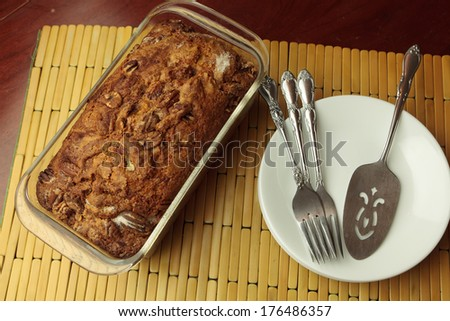 Sweet bread in the baking pan ready to be sliced and served with plates in the background - stock photo