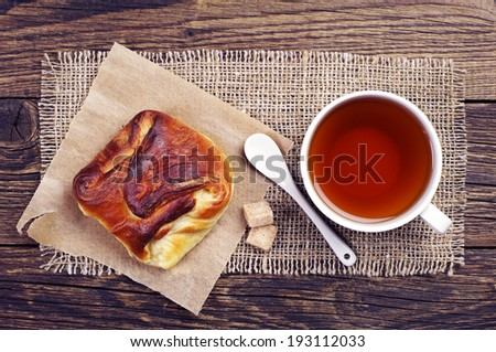 Sweet bun and cup of tea on wooden table. Top view - stock photo