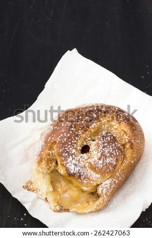 Sweet bun on black wooden background - stock photo