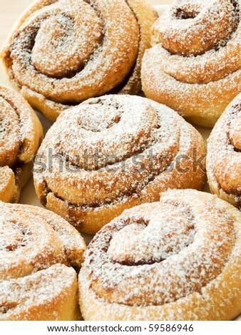 Sweet buns with cinnamon and powdered sugar. Shallow dof. - stock photo