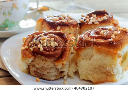 Sweet buns with cinnamon, nuts and caramel syrup. Shallow DOF - stock photo