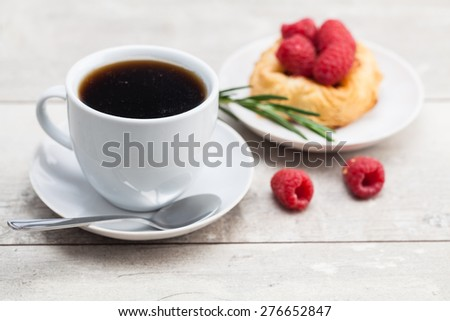 sweet cake with cup of tea on wooden table - stock photo