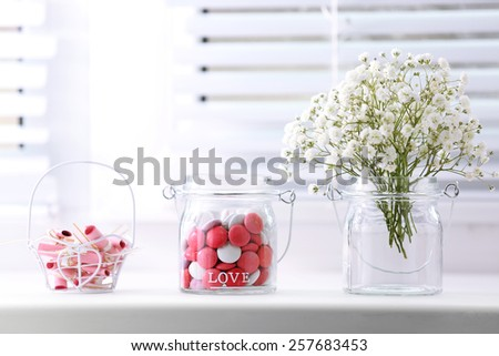 Sweet candies in jar with flowers on windowsill background - stock photo