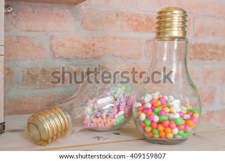 Sweet candies in lightbulb jar container, creative sweet ideas for birthday party, Vintage brick wall background, selective focus - stock photo