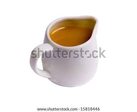 Sweet caramel sauce in white sauce-boat on white ground - stock photo