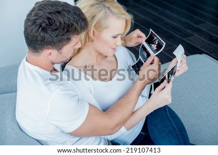 Sweet Caucasian Couple on Couch Looking Ultrasound Result Together - stock photo