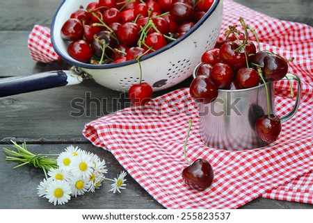 Sweet cherries on a wooden table in the garden - stock photo