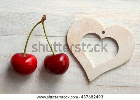 sweet cherries with a wooden decorative heart on wooden background - stock photo