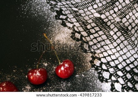 Sweet cherry against black background and lacy drawing from icing sugar - stock photo