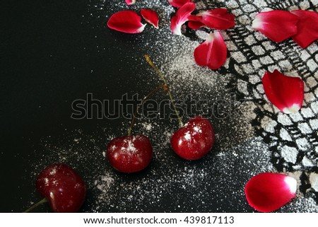 Sweet cherry against black background, lacy drawing from icing sugar and red rose petals - stock photo