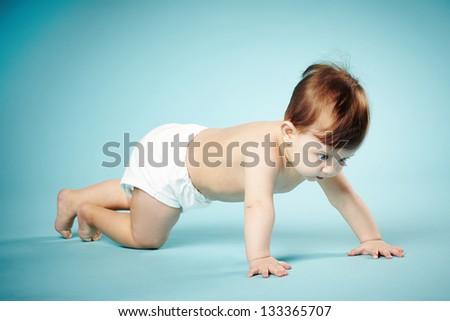 sweet child crawls on blue background - stock photo