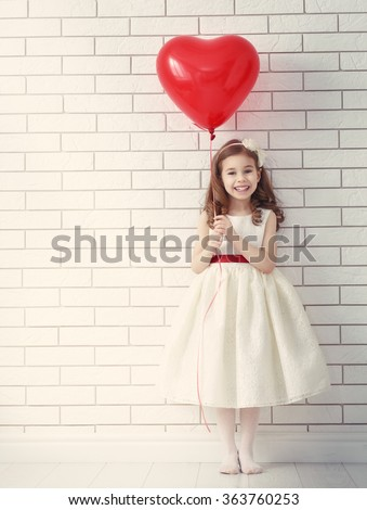 Sweet child girl with red heart. Happy little girl with red balloon at a blank brick wall. Wedding, Valentine concept. - stock photo