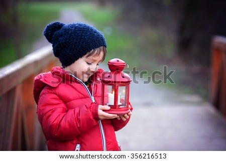 Sweet child, holding red lantern in the park on a sunny winter day, outdoors - stock photo