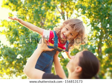 Sweet child playing airplane with her mom. Tilt shift effect. - stock photo