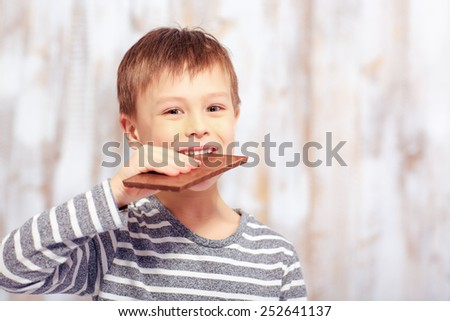 Sweet childhood. Portrait of an adorable little boy eating a bar of chocolate with happy face expression - stock photo
