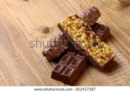 Sweet chocolate bars and peanut brittle on brown wooden table top background copy space, horizontal photo - stock photo