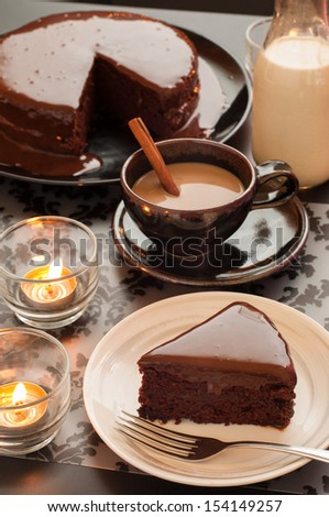 Sweet chocolate cake dessert, cup of coffee, bottle of milk and candlelight on the table. - stock photo