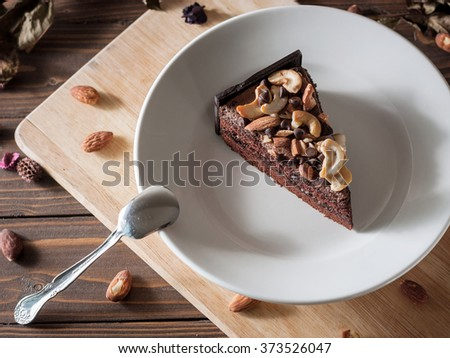 Sweet chocolate cake topping with chocolate and almond nut decorate with dried flower on wooden background - stock photo