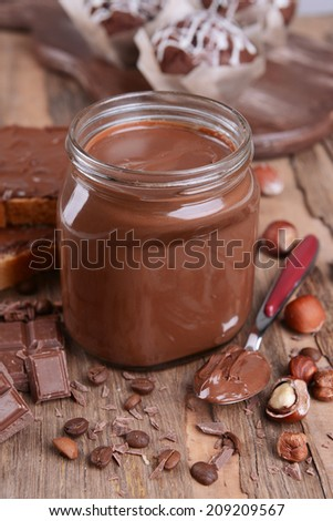 Sweet chocolate cream in jar on table close-up - stock photo