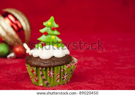 sweet christmas cupcake decorating with icing and sprinkles on a red background - stock photo