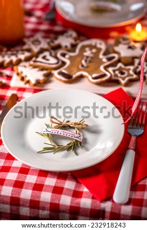 Sweet Christmas decorated table with candles, cookies, drinks and lights on background on red checkered tablecloth - stock photo