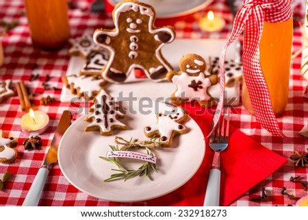 Sweet Christmas decorated table with ginger cookies, candles, drinks on red checkered tablecloth - stock photo