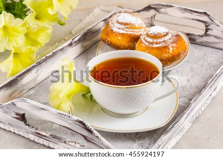 Sweet cinnamon bun rolls and cup of tea on vintage  serving tray. Breakfast Danish pastry and tea cup with yellow flowers. Breakfast tea with sweet pastry.  - stock photo