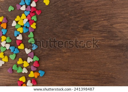 sweet color candies on heart-shaped cakes on a wooden background - stock photo