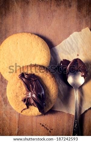 Sweet cookies with chocolate cream on wooden table  - stock photo